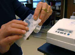 Figure 3.39: Holding the Petri dish between your thumb and middle, ring and pinkey fingers, use your index finger to pinch one end of the parafilm to the top and bottom of the Petri dish (covering the opening). Image by Dr. Marisa Pedulla.