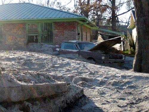 Figure 3.6: Silt deposits around a house and car in New Orleans left by flooding after Hurricane Katrina. This image is licensed under a GNU Free Documentation License, and comes from URL: http://upload.wikimedia.org/wikipedia/commons/d/da/SiltyMustang3Jan.jpg