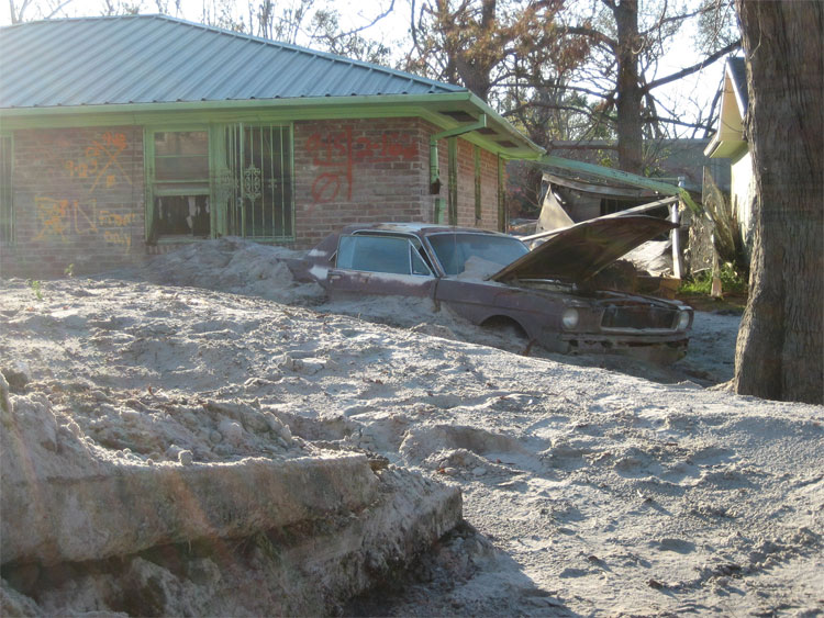 Figure 9.10: Silt deposits around a house and car in New Orleans left by flooding after Hurricane Katrina. Image from URL: http://upload.wikimedia.org/wikipedia/commons/d/da/SiltyMustang3Jan.jpg